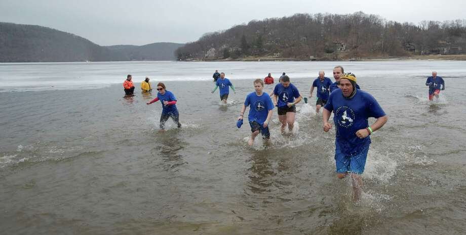 Participants in the Danbury Penguin Plunge run out of Candlewood Lake on Saturday, March 22, 2014. The event raised money and awareness for the Special Olympics, and took place at Candlewood Lake Park, Danbury, Conn. Photo: H John Voorhees III / The News-Times Freelance