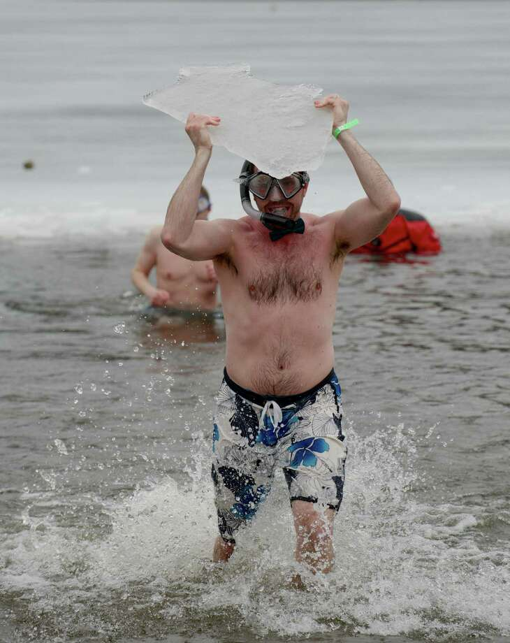John Wells, of Waterbury, makes his way out of Candlewood Lake  as part of the Penguin Plunge, which raised money and awareness for Special Olympics. He is carrying a chunk of ice he swam out and grabbed. The plunge took place at Candlewood Lake Park, Danbury, Conn, on Saturday, March 22, 2014. Wells said the reason he grabbed the ice was because he saw someone else do it and he wanted to get a bigger piece, but once he got in the water he was so cold he grabbed the first chunk of ice he found and made his way back to dry land. He wore the goggles and snorkel are just for the fun of it and said it was his firs time doing the event. Photo: H John Voorhees III / The News-Times Freelance