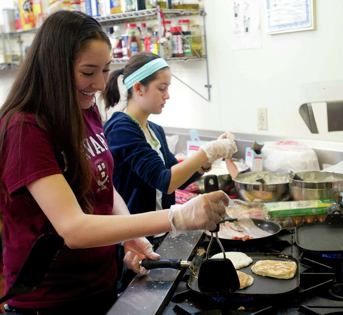 Westhill buildOn students Nancy Juarez, left, and Kelly Finn, right, make pancakes and bacon as they prepare breakfast at Inspirica for residents of the shelter on Saturday, March 22, 2014. The students competed against buildOn students from area schools to make meals using ingredients they collected from food drives for the Top Chef Cooking Competition.