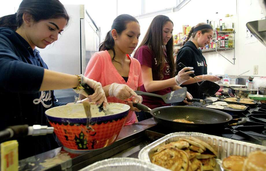 Westhill buildOn students, from left, Yamila Marrero, Gaby Nunez, Nancy Juarez, and Julia Schaffer prepare breakfast at Inspirica for residents of the shelter on Saturday, March 22, 2014. The students competed against buildOn students from area schools to make meals using ingredients they collected from food drives for the Top Chef Cooking Competition. Photo: Lindsay Perry / Stamford Advocate