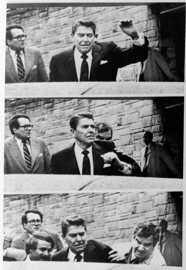 President Reagan waves, then looks up before being shoved into the Presidential limousine by Secret Service agents after being shot outside a Washington hotel in this photo sequence. Photo: RON EDMONDS, STF / AP