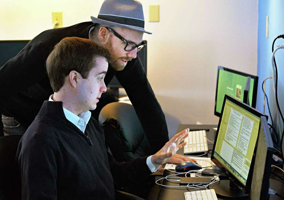 Co-owners Peter Allegretti, top, and Michael Tanski at work inside the garage that houses their Doctored Apps offices Thursday Feb. 27, 2014, in Colonie, NY.  (John Carl D'Annibale / Times Union) Photo: John Carl D'Annibale / 00025938A