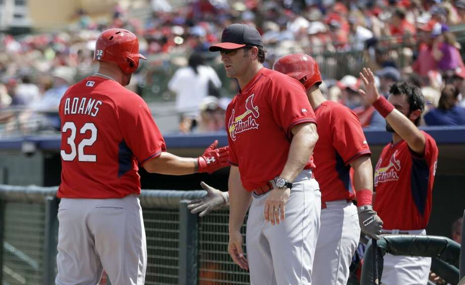 Matt Adams is greeted by manager Mike Matheny after scoring in the first inning. Photo: Carlos Osorio, Associated Press