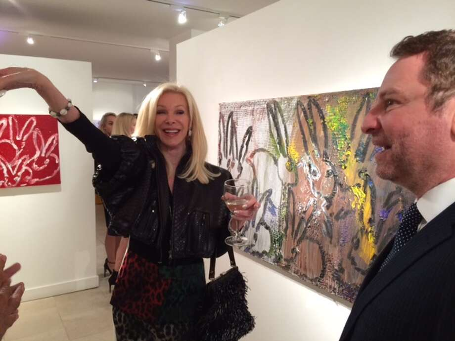 Art collector Pamala Deikel is exuberant about one of the bunny paintings, as Serge Sorokko looks on.