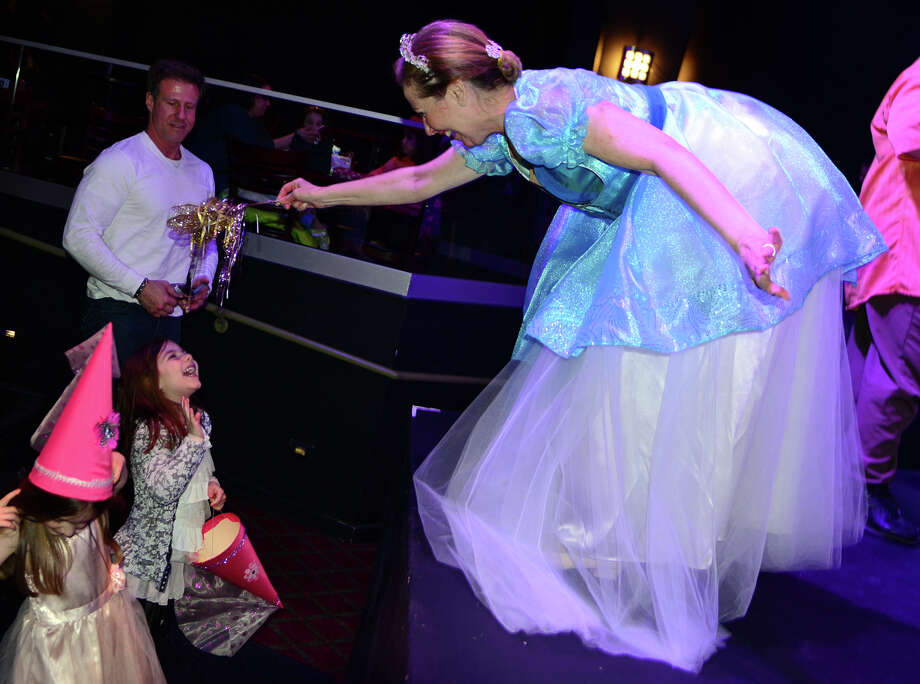 "Using her magic wand, the Ballerina Princess, Linda Giancaspro, sprinkles fairy dust onto one of the girls attending New England Ballet Company's ""Ballerina Princess Party"" held at the Bijou Theater in downtown Bridgeport, Conn. on Saturday March 22, 2014. The young girls who attended the shows at 11 a.m. and 2 p.m., danced with the ballerinas, and learned how to wave like a princess. Guests also learned a ""court"" dance with Princess Linda and how to make a Princess craft including tiaras. Photo: Christian Abraham / Connecticut Post"