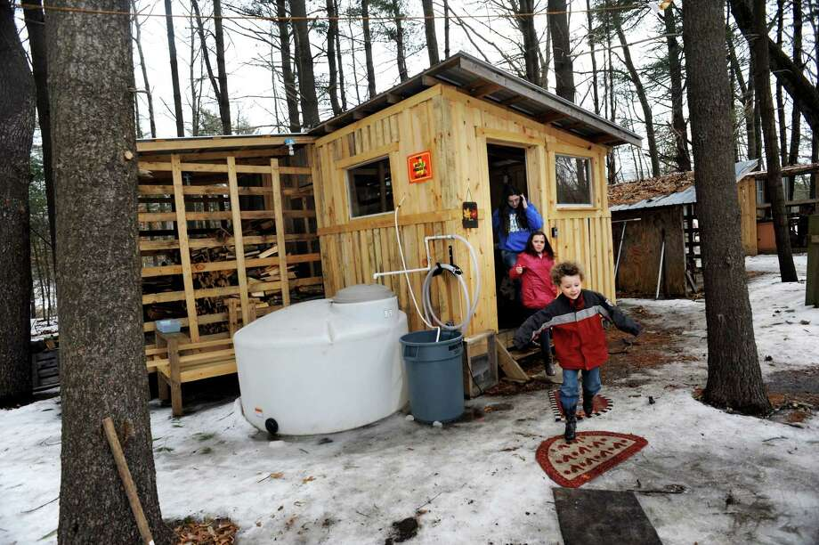 Tommy Burke, 5, of Guilderland, front, runs out of the sugar shack with his cousins Carly Burke, 9, center, and Lily Burke, 12, during a tour on Saturday, March 22, 2014, at Sugar Oak Farms in Malta, N.Y. The Maple Open House Weekends, put on by the Upper Hudson Maple Producers Association, continues Sunday and next weekend from 10 a.m. to 4 p.m. each day, allowing the public to take a free tour of area sugarhouses. (Cindy Schultz / Times Union) Photo: Cindy Schultz / 00026217A