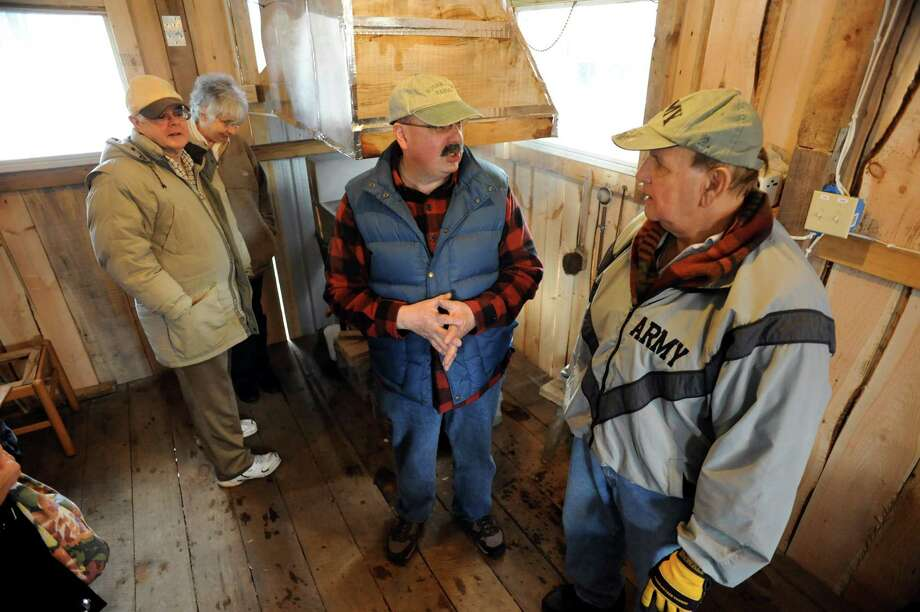 Syrup maker Erich Ruger, center, talks with visitors during a tour on Saturday, March 22, 2014, at Sugar Oak Farms in Malta, N.Y. From left are Jim and Mary Weekes of Ballston Lake and Al Bertrand of Clifton Park. The Maple Open House Weekends, put on by the Upper Hudson Maple Producers Association, continues Sunday and next weekend from 10 a.m. to 4 p.m. each day, allowing the public to take a free tour of area sugarhouses. (Cindy Schultz / Times Union) Photo: Cindy Schultz / 00026217A