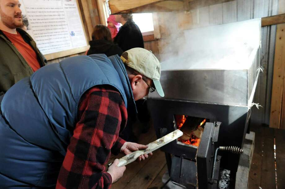 Syrup maker Erich Ruger, center, stokes the fire to evaporate water off the sap in the sugar shack on Saturday, March 22, 2014, at Sugar Oak Farms in Malta, N.Y. The Maple Open House Weekends, put on by the Upper Hudson Maple Producers Association, continues Sunday and next weekend from 10 a.m. to 4 p.m. each day, allowing the public to take a free tour of area sugarhouses. (Cindy Schultz / Times Union) Photo: Cindy Schultz / 00026217A