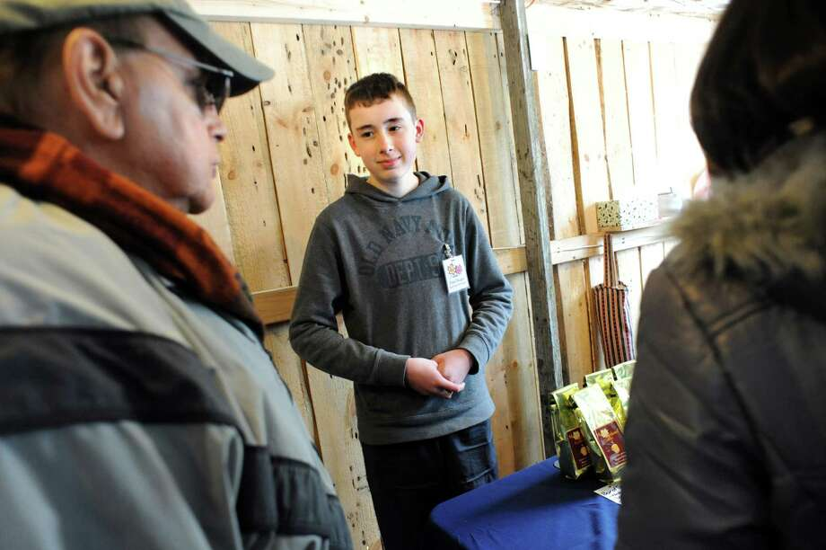 Paul Ruger, 14, center, who's been making syrup with his father for six years, talks with Al Bertrand of Clifton Park , left, in the sugar shack on Saturday, March 22, 2014, at Sugar Oak Farms in Malta, N.Y. The Maple Open House Weekends, put on by the Upper Hudson Maple Producers Association, continues Sunday and next weekend from 10 a.m. to 4 p.m. each day, allowing the public to take a free tour of area sugarhouses. (Cindy Schultz / Times Union) Photo: Cindy Schultz / 00026217A