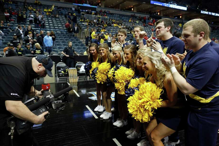 Michigan cheerleaders pose for the TV camera before  a third-round game of the NCAA college basketball tournament between the Michigan and the Texas Saturday, March 22, 2014, in Milwaukee. (AP Photo/Jeffrey Phelps) Photo: Jeffrey Phelps, Associated Press / FR59249 AP