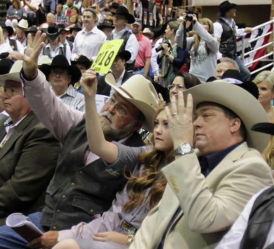 Ed Lester, left, and fourteen-year-old Rhianna Bruegger, center, and Bruegger's father Chris Bruegger, right, bid on Flint Newman's Charolais Grand Champion steer during the Houston Livestock Show and Rodeo 2014 Junior Market Steer Auction at Reliant Arena Saturday, March 22, 2014, in Houston. Photo: James Nielsen, Houston Chronicle / © 2014  Houston Chronicle