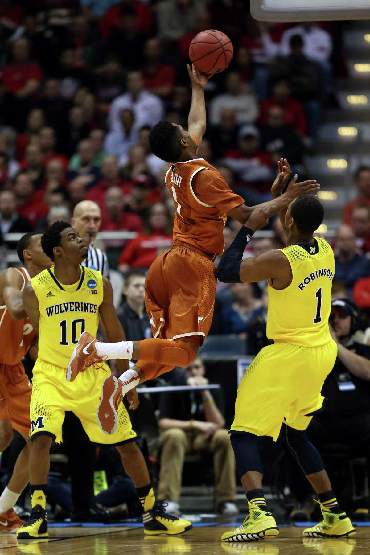 MILWAUKEE, WI - MARCH 22: Isaiah Taylor #1 of the Texas Longhorns shoots the ball over Glenn Robinson III #1 of the Michigan Wolverines during the third round of the 2014 NCAA Men's Basketball Tournament at BMO Harris Bradley Center on March 22, 2014 in Milwaukee, Wisconsin.