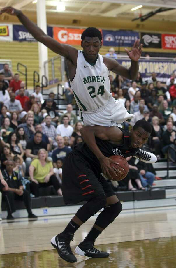 Moreau Catholic's Oscar Frayer soars over Salesian's Derek E'Denchukwu in the first half of the Mariners' 61-52 win at American Canyon High School. Photo: Paul Chinn, The Chronicle