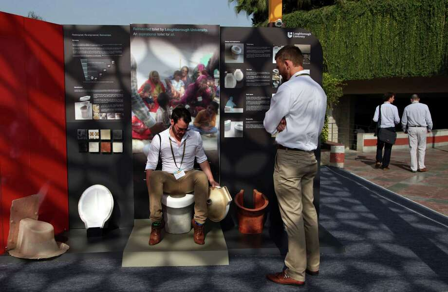 An exhibitor from Loughborough University demonstrates the use of a toilet during Reinvent the Toilet Fair in New Delhi, India, last week. Photo: Tsering Topgyal, STR / AP