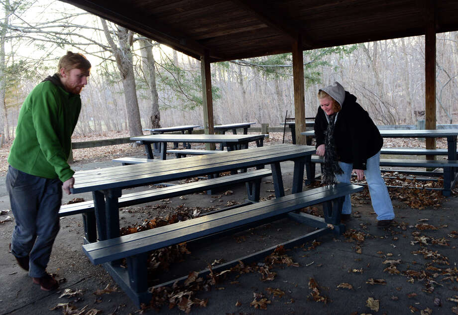 Ansonia Nature Center volunteer Michael Karolowski, left, and Ranger Dawn Sotir, move picnic tables into a circle before holding a drum circle at the nature center in Ansonia, Conn. on Saturday March 22, 2014. Drums and other percussion instruments were used by the fire to gently wake up Earth to celebrate the start of the vernal equinox. Photo: Christian Abraham / Connecticut Post