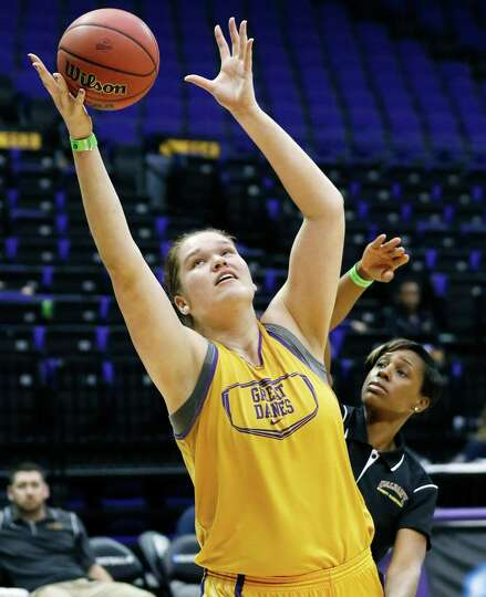Albany center Megan Craig stretches for a ball while a coach defends during practice at the NCAA wom