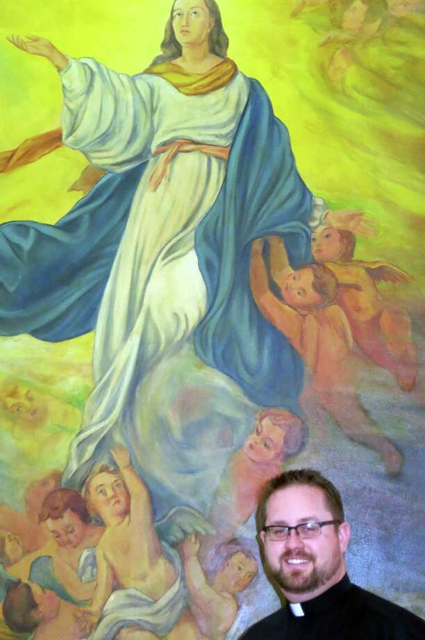 Father Daniel Dreher said the angel on the Assumption painting is modeled after a daughter of one of the Italian POWs. Decades later she visited the church. Photo: Joe Holley