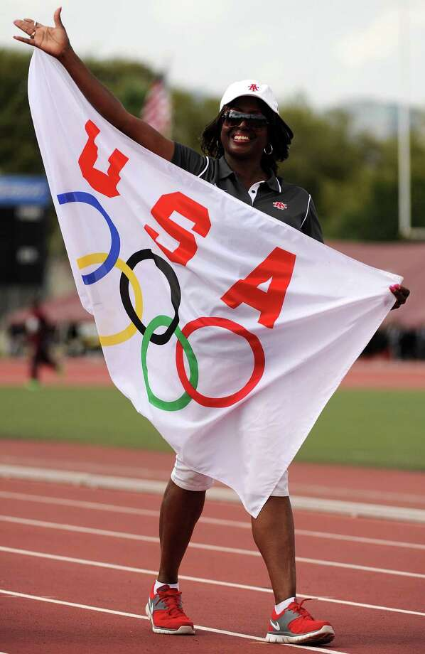 Karen Hawkins carries a USA olympic team flag for the 1980s decade team before the TSU Relays, Saturday, March 22, 2014, at Durley Stadium in Houston. Hawkins was going to be a competitor in the 200 meter race for the USA olympic team in the 1980 Olympic Games in Moscow, but the United States boycotted the games. Photo: Eric Christian Smith, For The Chronicle