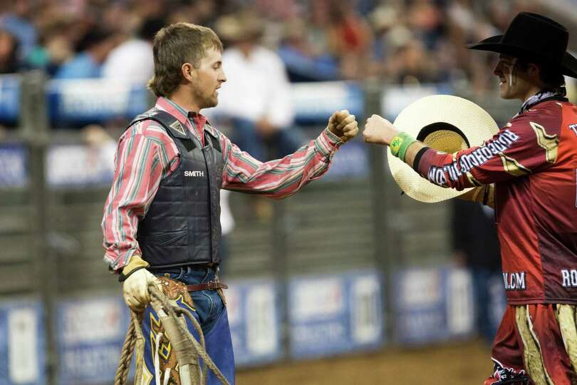 Bull rider Tyler Smith, left, bump fists with bullfighter Dusty Tuckness after winning the Bull Ridi