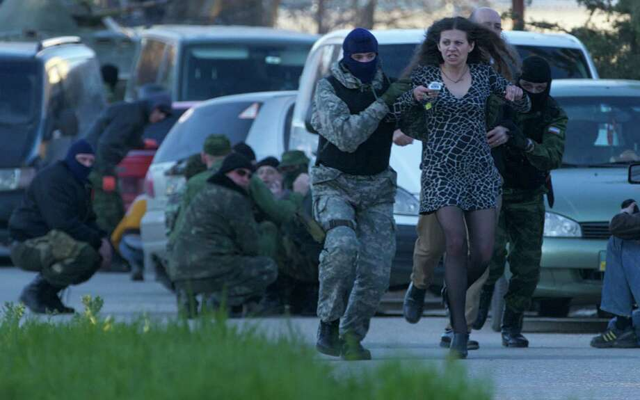 Pro-Russian militia members evacuate a resident Saturday as Russian troops assault the Belbek airbase outside Sevastopol, Crimea. Russian forces took over one of the last Ukrainian military outposts in Crimea. Photo: Ivan Sekretarev, STF / AP