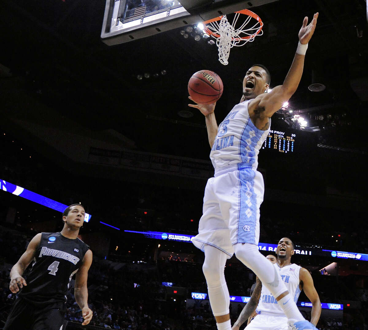 North Carolina's J.P. Tokoto (13) reacts after a dunk as Providence's Josh Fortune (04) looks on during first half action of their second round 2014 NCAA Division I Men's Basketball Championship held Friday March 21, 2014 at the AT&T Center.