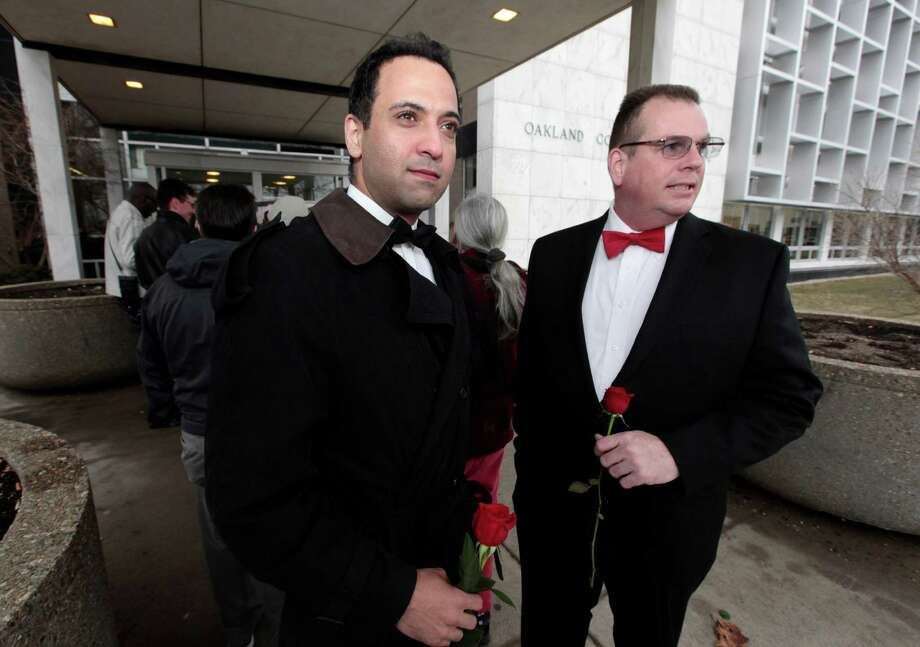 Nasir Khawaja, left, and Mark Sarver stand outside in line to apply for a marriage license at the Oakland County Clerks office in Pontiac, Mich., Saturday, March 22, 2014. A federal judge has struck down Michigan's ban on gay marriage Friday the latest in a series of decisions overturning similar laws across the U.S. Some counties plan to issue marriage licenses to same-sex couples Saturday, less than 24 hours after a judge overturned Michigan's ban on gay marriage. (AP Photo/Paul Sancya) Photo: Paul Sancya, STF / AP