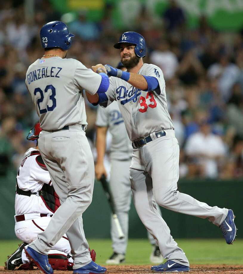 Adrian Gonzalez (left) congratulates Scott Van Slyke after Van Slyke hit a two-run home run in the Dodgers' 3-1 season-opening victory against the Diamondbacks in Sydney. Photo: Rick Rycroft / Associated Press / AP