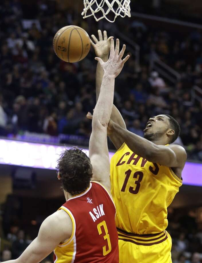 Tristan Thompson of the Cavaliers attempts a shot against Rockets center Omer Asik. Photo: Tony Dejak, Associated Press