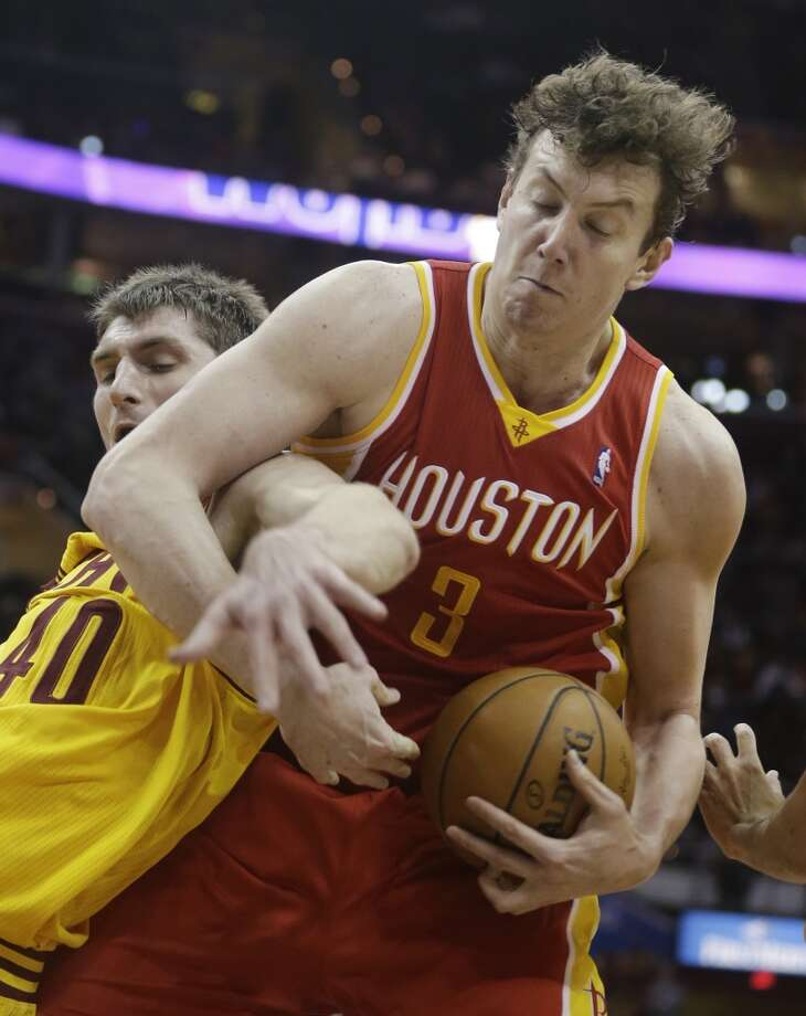 Rockets center Omer Asik fights for possession of the ball against Tyler Zeller of the Cavaliers. Photo: Tony Dejak, Associated Press