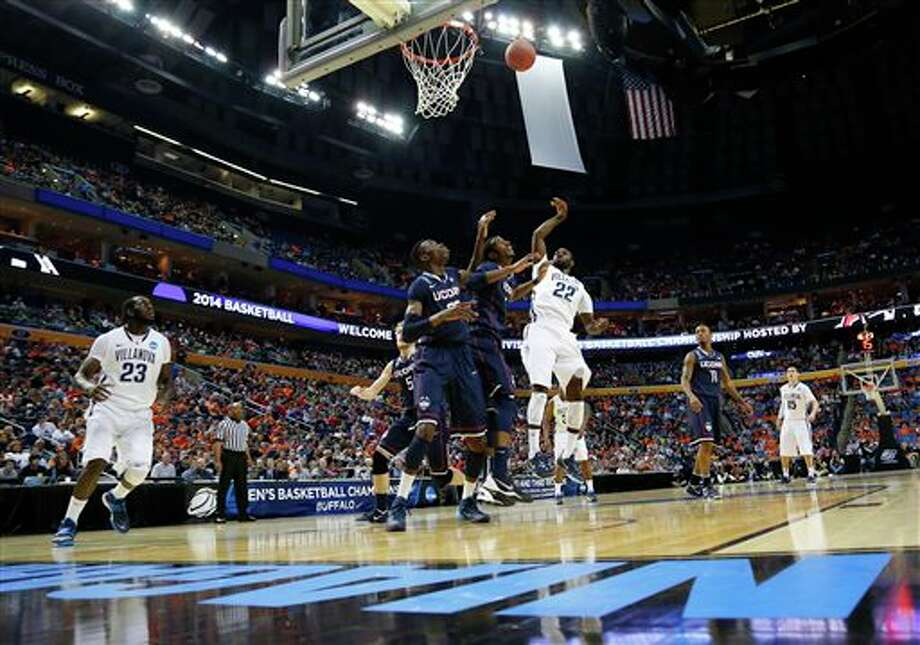 Villanova's JayVaughn Pinkston (22) shoots over Connecticut's DeAndre Daniels and  Amida Brimah (35) during the first half of a third-round game in the  NCAA men's college basketball tournament in Buffalo, N.Y., Saturday,  March 22, 2014. (AP Photo/Bill Wippert)