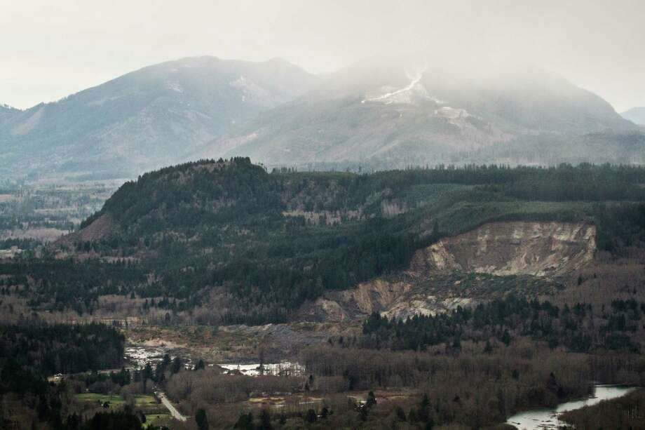 A wide aerial view shows the extensive damage of the landslide after taking out a chunk of Earth from the side of the hill facing the Stillaguamish River, and down into state Route 530, on the left, between the cities of Arlington and Darrington, on Saturday, March 22, 2014. Search and rescue operations are underway for survivors. Photo: Marcus Yam/The Seattle Times/via AP / The Seattle Times