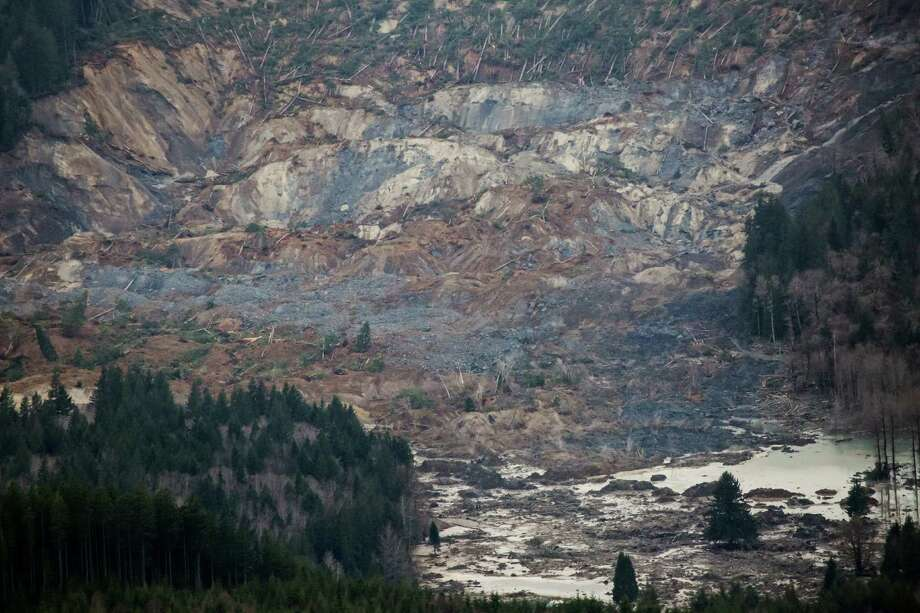 An aerial view shows a huge volume of earth missing from the side of a hill facing Stillaguamish River, in a landslide along State Route 530, between the cities of Arlington and Darrington, on Saturday, March 22, 2014. Search and rescue operations are underway for survivors. Photo: Marcus Yam/The Seattle Times/via AP / Digital Image