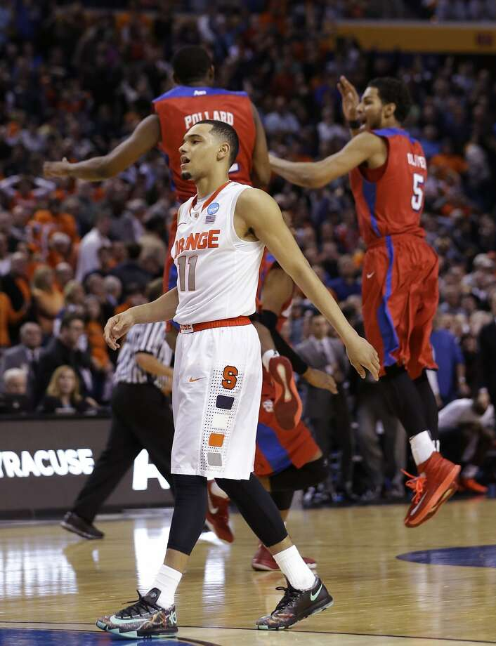 Syracuse's Tyler Ennis stays low to the ground after missing a potential game-winner, while Dayton players leap for joy. Photo: Frank Franklin II, Associated Press