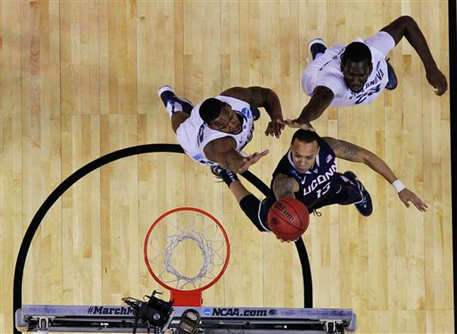 Connecticut's Shabazz Napier drives past Villanova's JayVaughn Pinkston, left, and Daniel Ochefu (23) during the first half  of a third-round game in the NCAA men's college basketball tournament in  Buffalo, N.Y., Saturday, March 22, 2014. (AP Photo/Bill Wippert)