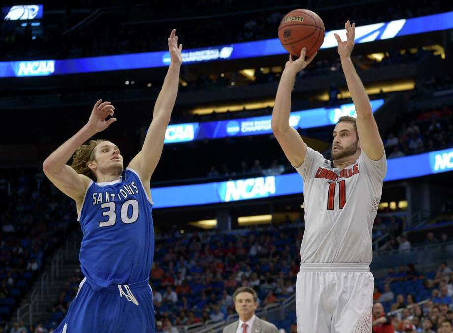 Louisville forward Luke Hancock (11) shoots a 3-point shot as Saint Louis forward Jake Barnett (30) defends during the second half in a third-round game in the NCAA college basketball tournament  Saturday, March 22, 2014, in Orlando, Fla. Louisville won  66-51. (AP Photo/Phelan M. Ebenhack) ORG XMIT: DOA159 Photo: Phelan M. Ebenhack / FR121174 AP