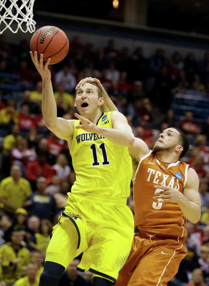 Texas' Javan Felix, right, makes sure Michigan's Nik Stauskas can't get up a head of steam. Photo: Jeffrey Phelps, FRE / FR59249 AP