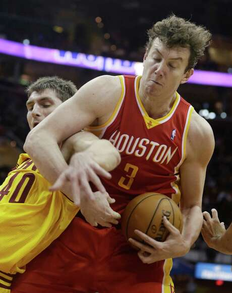 Rockets center Omer Asik (3), subbing for an injured Dwight Howard, becomes entangled with the Cavaliers' Tyler Zeller while trying to control a rebound. Photo: Tony Dejak, STF / AP