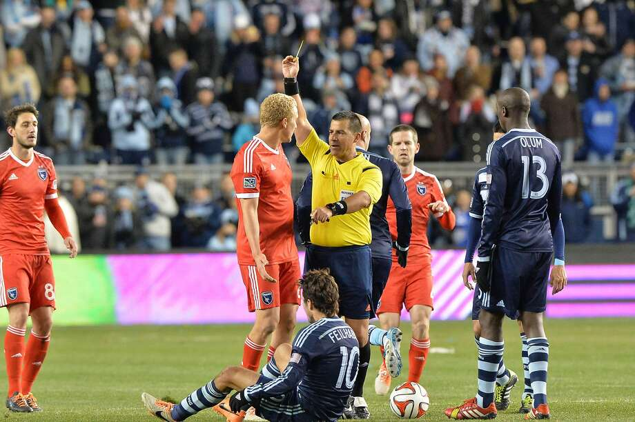 San Jose's Steven Lenhart is shown a yellow card by referee Ricardo Salazar. Photo: Peter Aiken, Reuters