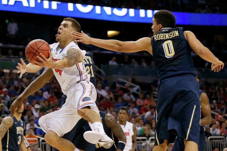 Florida's Scottie Wilbekin glides past Pittsburgh's James Robinson (0) for two of his 21 points Saturday. Photo: Kevin C. Cox, Staff / 2014 Getty Images