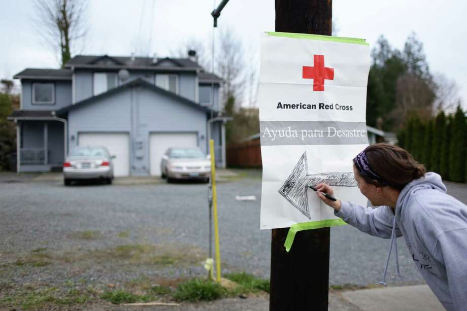 A sign is placed to direct those in need to a Red Cross shelter at Post Middle School in Arlington, Wash. A massive landslide destroyed homes, killed three people and created a dam on the North Fork of the Stillaguamash River creating a dangerous flooding possibility. Photographed on Saturday, March 22, 2014. Photo: JORDAN STEAD, SEATTLEPI.COM / SEATTLEPI.COM