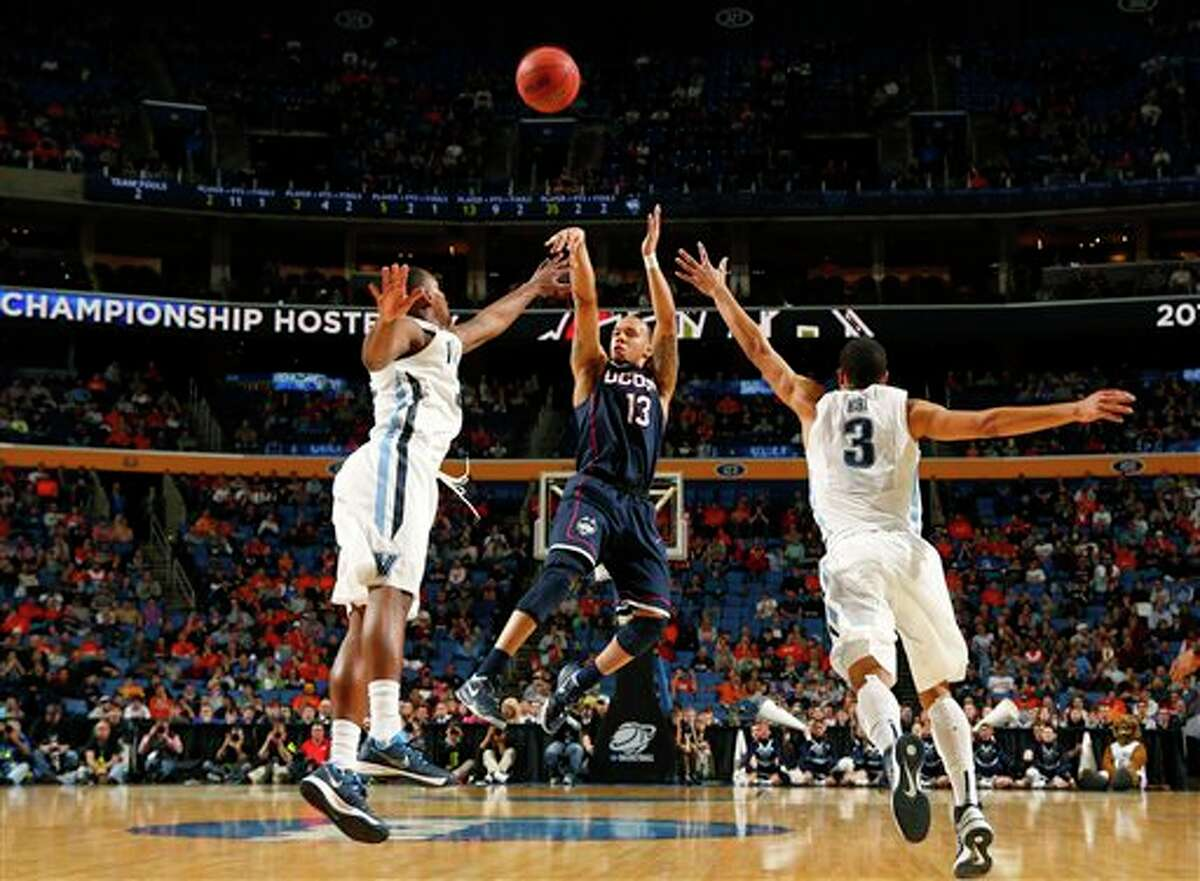 Villanova's Josh Hart (3) runs out to defend Connecticut's Shabazz Napier (13) during the second half of a third-round game in the NCAA men's college basketball tournament in Buffalo, N.Y., Saturday, March 22, 2014. (AP Photo/Bill Wippert)