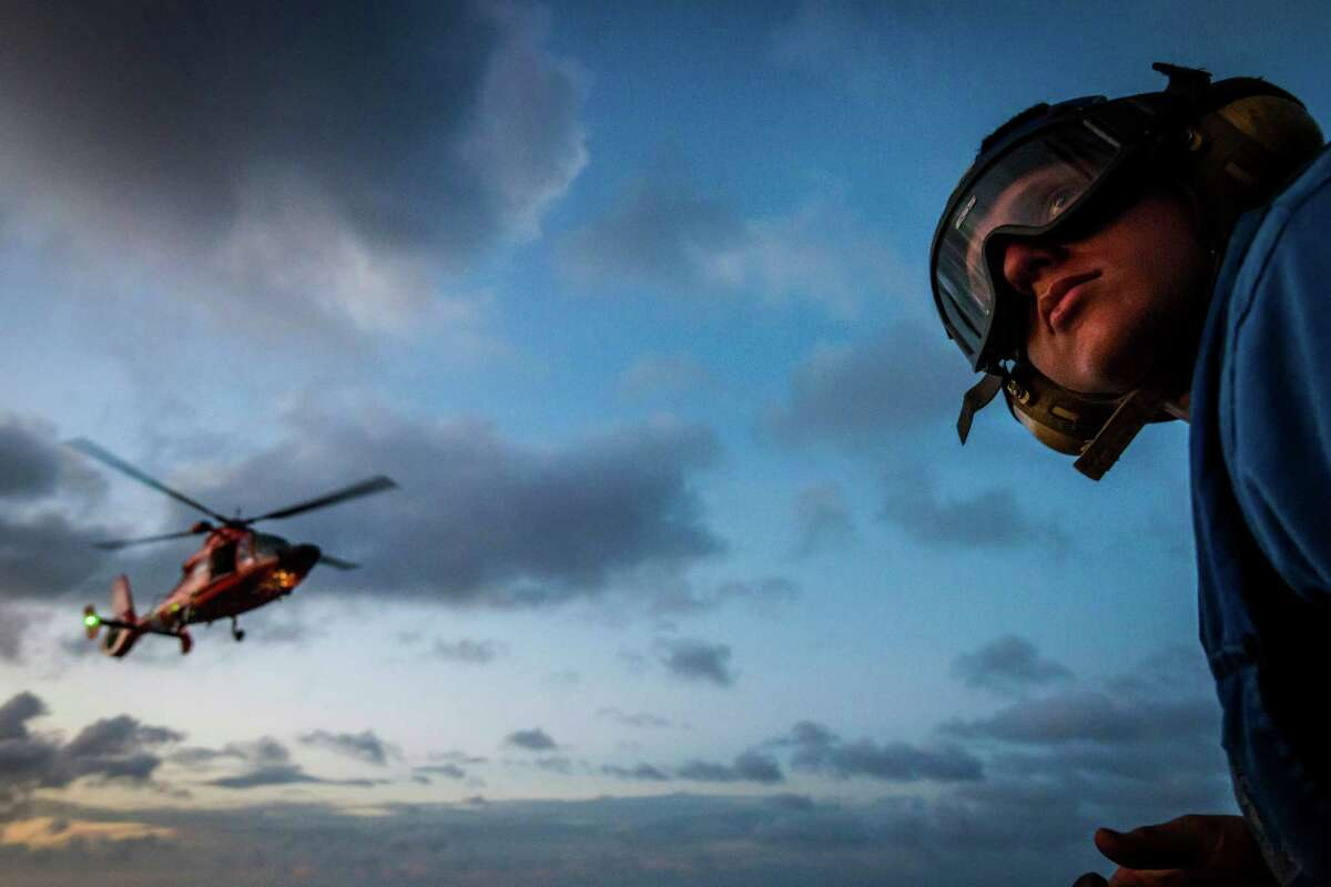 Seaman Justin Baker works on the flight deck of the Coast Guard Cutter Dauntless as a helicopter approached for landing on the ship while on patrol in Caribbean Sea. ( Smiley N. Pool / Houston Chronicle )