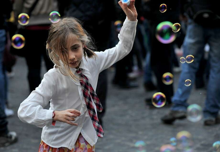 A girl plays with soap bubbles during a flash mob near the Pantheon on March 22, 2014 in Rome.  TOPSHOTS/AFP PHOTO/TIZIANA FABITIZIANA FABI/AFP/Getty Images Photo: Tiziana Fabi, AFP/Getty Images