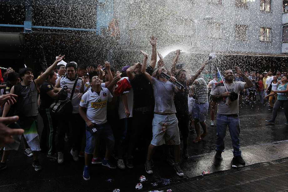 Water rains down on a group of demonstrators, released by residents of surrounding buildings to cool off the marchers, during a massive demonstration of more than 30 activist groups pressing newly installed President Michelle Bachelet to follow through with her campaign promises, in Santiago, Chile, Saturday, March 22, 2014. (AP Photo / Luis Hidalgo) Photo: Luis Hidalgo, Associated Press