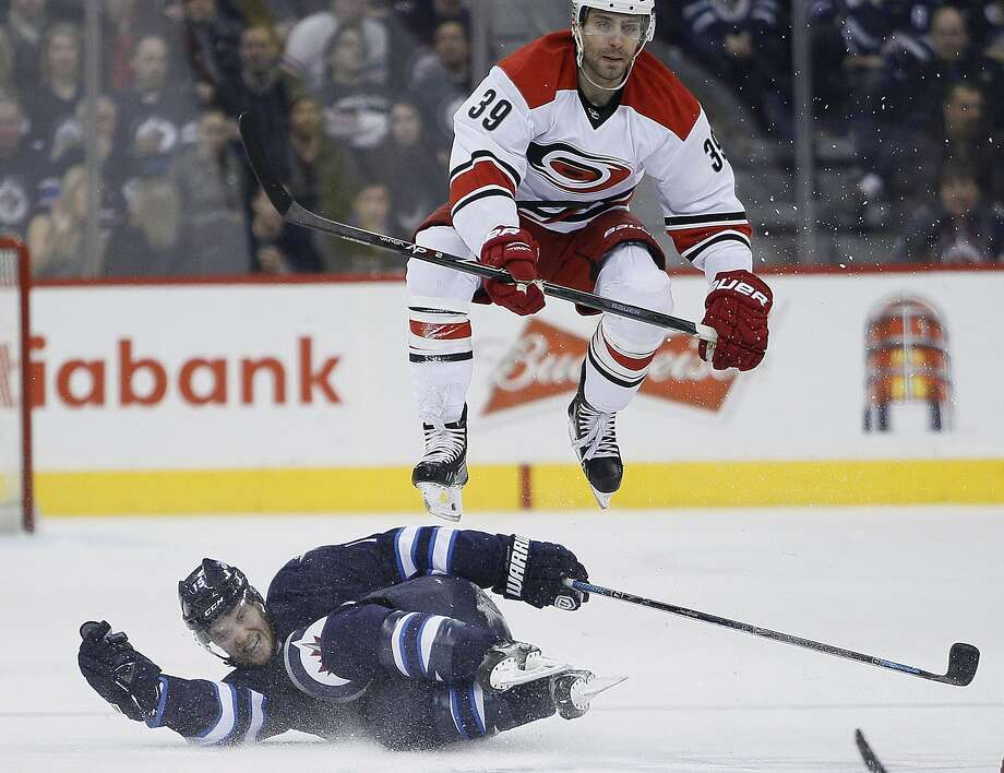 Carolina Hurricanes' Patrick Dwyer (39) leaps over Winnipeg Jets' Matt Halischuk (15) during the second period of an NHL hockey game, Saturday, March 22, 2014, in Winnipeg, Manitoba. (AP Photo/The Canadian Press, John Woods) Photo: John Woods, Associated Press