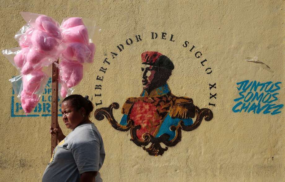 A cotton candy vendor stands next to a mural of Venezuela's late President Hugo Chavez as she watches a gathering between President Nicolas Maduro and students in Caracas, Venezuela, Saturday, March 22, 2014. Two more people were reported dead in Venezuela as a result of anti-government protests even as supporters and opponents of Maduro took to the streets on Saturday in new shows of force. (AP Photo/Esteban Felix) Photo: Esteban Felix, Associated Press