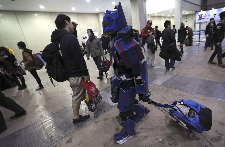 "A costume player, or cosplayer, with cardboard-made robot costume walks around with his belonging during AnimeJapan 2014 anime festival in Tokyo, Saturday, March 22, 2014. Cosplay, or ""costume play,"" is a growing art form in which fans create detailed costumes to accurately represent their favorite characters in pop culture. (AP Photo/Eugene Hoshiko) Photo: Eugene Hoshiko, Associated Press"