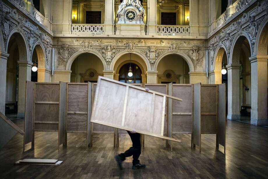 TOPSHOTS A municipal employee prepares a polling station on March 22, 2014 in Lyon, on the eve of the 2014 French municipal election first round. AFP PHOTO / JEFF PACHOUDJEFF PACHOUD/AFP/Getty Images Photo: Jeff Pachoud, AFP/Getty Images