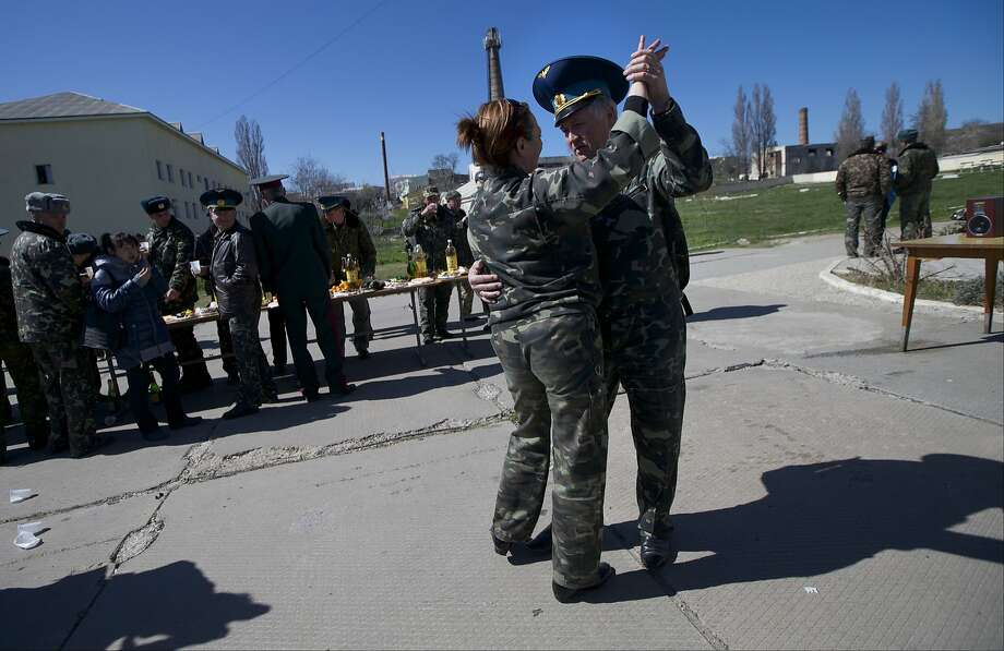 Ukrainian airmen dance as they celebrate their comrade's wedding at the Belbek airbase outside Sevastopol, Crimea, on Saturday, March 22, 2014. Two young Lieutenants, medic Galina Volosyanchik and communication officer Ivan Benera got married today and arrived to their unit for a short celebration as Russian troops continue to occupy part of the airbase and demand surrender of Ukrainian airmen. (AP Photo/Ivan Sekretarev) Photo: Ivan Sekretarev, Associated Press