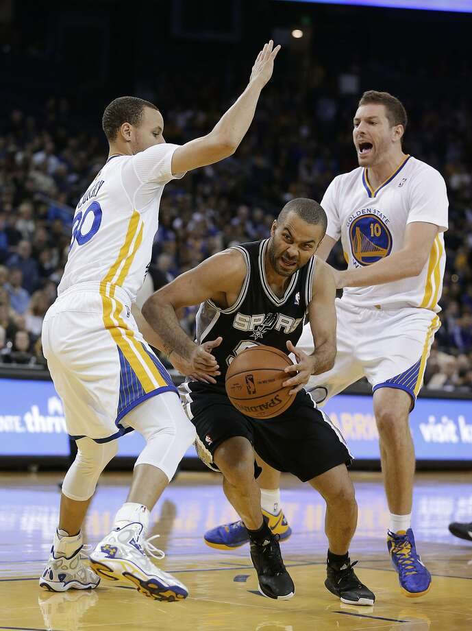 San Antonio guard Tony Parker drives between the Warriors' Stephen Curry (left) and David Lee in the first quarter. Parker led the Spurs with 20 points. Photo: Eric Risberg, Associated Press
